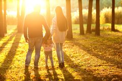 Family with little daughter spend fun time in autumn park at su Royalty Free Stock Photo
