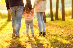 Family with little daughter spend fun time in autumn park at su Royalty Free Stock Photos