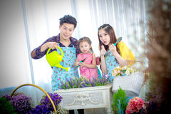 Family with little girl in Play gardening. Backlit shot Stock Photos