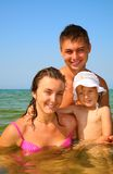 Family with little girl pose in sea Stock Image