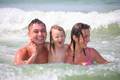 Family with little girl in waves Royalty Free Stock Photo