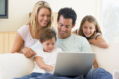 Family in living room with laptop smiling Royalty Free Stock Photos