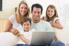 Family in living room with laptop smiling Stock Photo