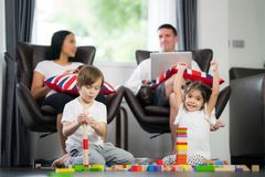 Family in living room play wooded toy. Family in living room, small kid, boy and girl play wooded toy Stock Image