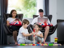 Family in living room small kid play wooded toy. Family in living room, small kid, boy and girl play wooded toy Stock Image