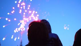 Family look at the sky at the fireworks. The night sky in lights stock footage