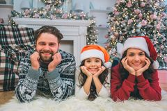 Family look. Young man, woman and ther daughter lying on floor and look on camera. They pose. eople hold hands under. Family look. Young man, women and ther royalty free stock image