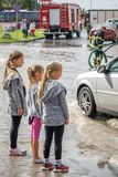 Three little girls looking at an aftermath of torrential rain Royalty Free Stock Photo