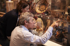 Family Looking At Artifacts In Glass Case On Trip To Museum stock photo