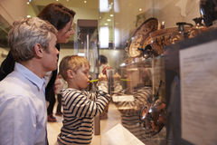 Family Looking At Artifacts In Glass Case On Trip To Museum Stock Photography
