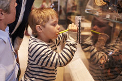 Family Looking At Artifacts In Glass Case On Trip To Museum Royalty Free Stock Image