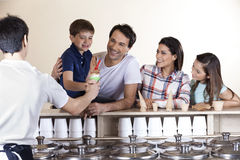 Family Looking At Boy While Waiter Serving Him Ice Cream