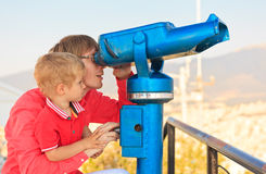 Family looking through binoculars at the city. Father and son looking at binoculars at the city Stock Image