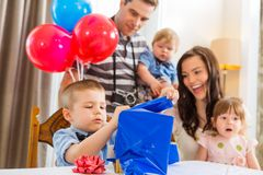 Family Looking At Birthday Boy Opening Gift Box Royalty Free Stock Photos
