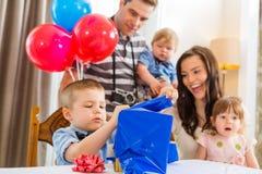 Family Looking At Birthday Boy Opening Gift Box Royalty Free Stock Photos