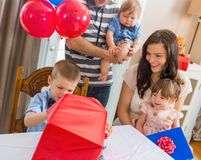 Family Looking At Birthday Boy Opening Gift Box Royalty Free Stock Images