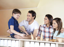 Family Looking At Boy Choosing From Cups And Cones Stock Photography