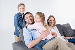 Family looking at camera while sitting on sofa together isolated on white Royalty Free Stock Photography