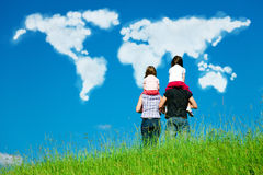 Family Looking At Clouds Forming The World Map. A family with 2 daughters are standing at the top of a grassy hill, looking at clouds in the form of the world`s Royalty Free Stock Images