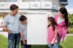 Family looking at a empty board outside house Royalty Free Stock Image