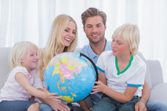 Family looking at globe together Stock Photo