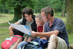 Family looking at hiking map. Family of three sitting down, looking at a map Stock Images