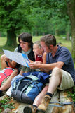 Family looking at hiking map. Family of three sitting down, looking at a map Royalty Free Stock Image