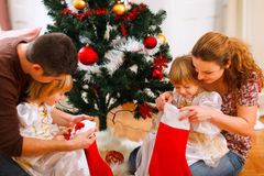 Family looking inside of Christmas socks near Royalty Free Stock Photos