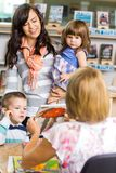 Family Looking At Librarian Showing Book. Mother and children looking at librarian showing book in library Stock Image