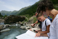 Family looking at a map by a river. Mother daughter and father taking a break from hiking to look at a map Stock Photography