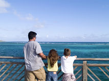 Family looking at the ocean. Father and two children standing on a wooden pier, looking at the ocean Stock Photos