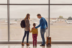 Family looking out window at airport Stock Photos