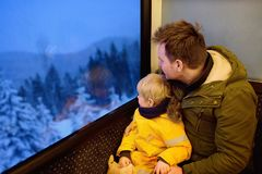 Family looking out of the window of train during travel on cogwheel railway/rack railway in Alps mountains. Winter holidays in Swiss/German/Italian Alps stock image