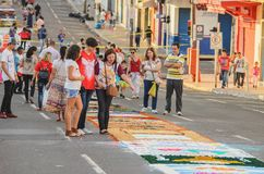 Family looking at the sawdust art on the street. Campo Grande, Brazil - May 31, 2018: Holiday event of Corpus Christi at the 14 de Julho street. People at the Royalty Free Stock Photo