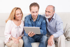 Family looking at a screen. Younger men with elderly persons checking an electronic devise Stock Images