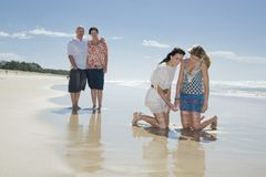 Family looking at shell on beach Royalty Free Stock Images