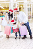 Family looking at shopping bags in mall Stock Image