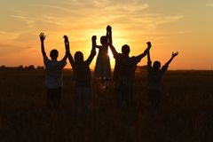 Family looking at sunset. Family holding hands looking at sunset in field Royalty Free Stock Photography
