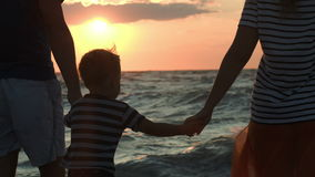Family looking at sunset holding hands. Family of three coming up to the wavy sea and they looking at sunset holding hands stock footage