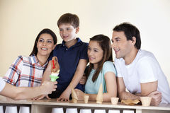 Family Looking At Waiter Giving Ice Cream At Counter Royalty Free Stock Photography