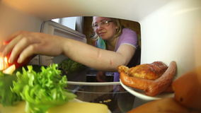 The family looks in the fridge .Everyone chooses for himself the products. stock video footage