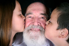 Family love. Children showing their love to their grandfather Stock Photo