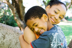 Family love. Concept: african mother hugging her teen boy outdoors stock photo