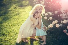Family love and care. Childhood and parenting. Family love and care. Woman with girl child at blossoming rose flowers. Mothers day concept. Mom cuddling stock image