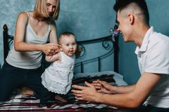 Parents teaching little baby girl to walk at home bed stock photo