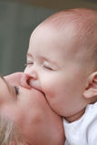 Family love - mother and son portrait kissing outdoors on a sunny day Royalty Free Stock Image