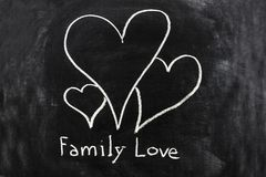 Family love sketched on the blackboard. A concept image with three hearts sketched on the blackboard to represent the family love royalty free stock photography