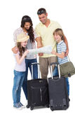 Family with luggage exploring map Stock Images