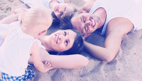 Family lying on beach, top view Royalty Free Stock Photos