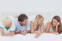 Family lying on the bed Stock Photos